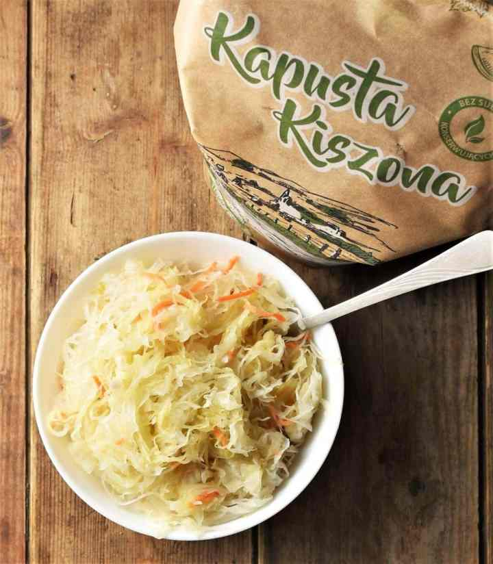 Top down view of sauerkraut in white bowl with spoon and sauerkraut packaging.
