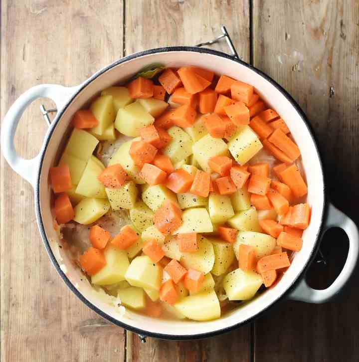 Cubed potatoes and carrots in large white pot.