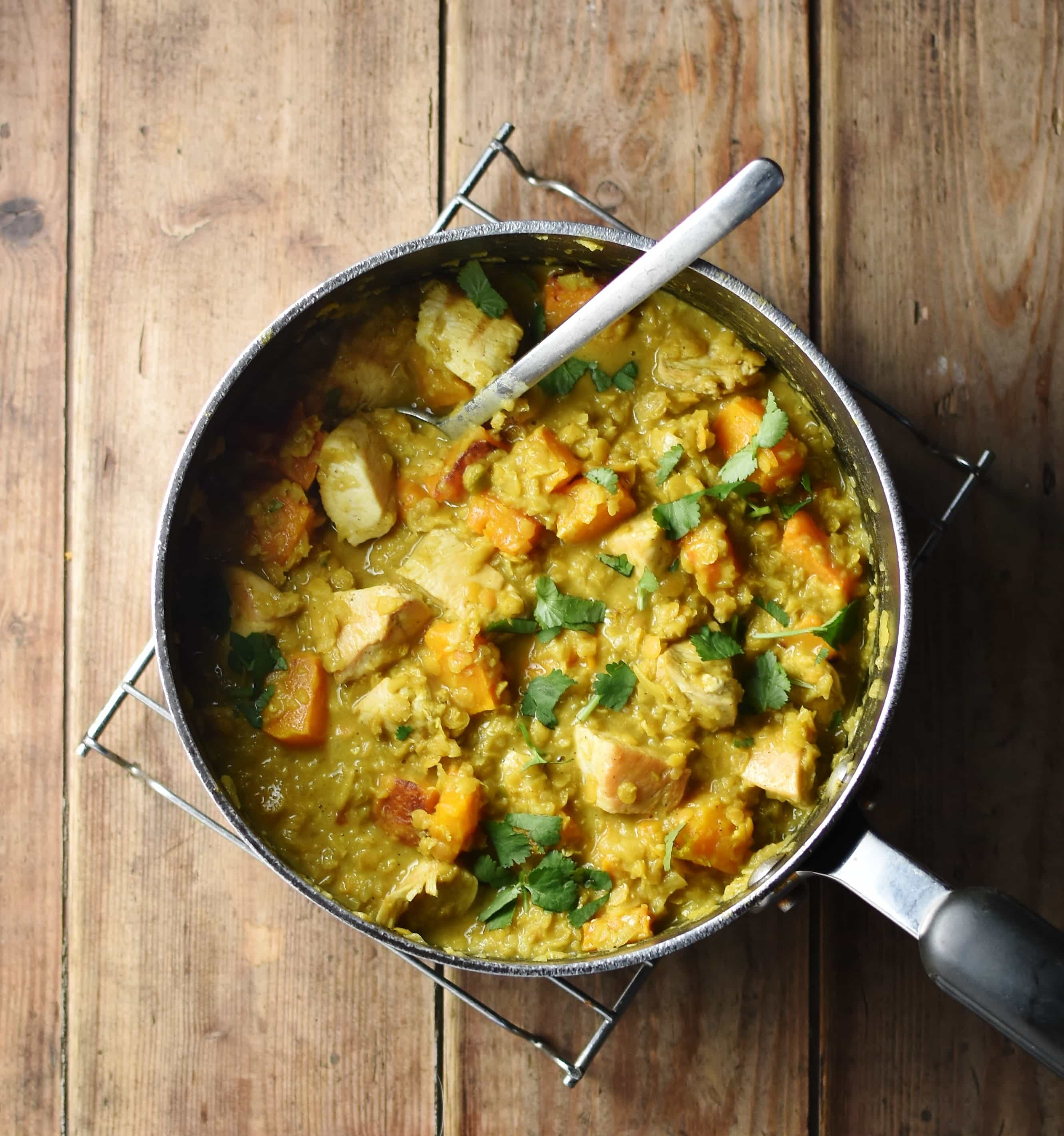 Chicken butternut squash curry with vegetables in large pot with spoon.