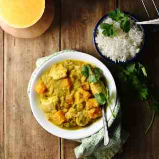 Chicken squash curry in white bowl with spoon wrapped in cloth, with rice in small bowl in top right and halved squash in top left.