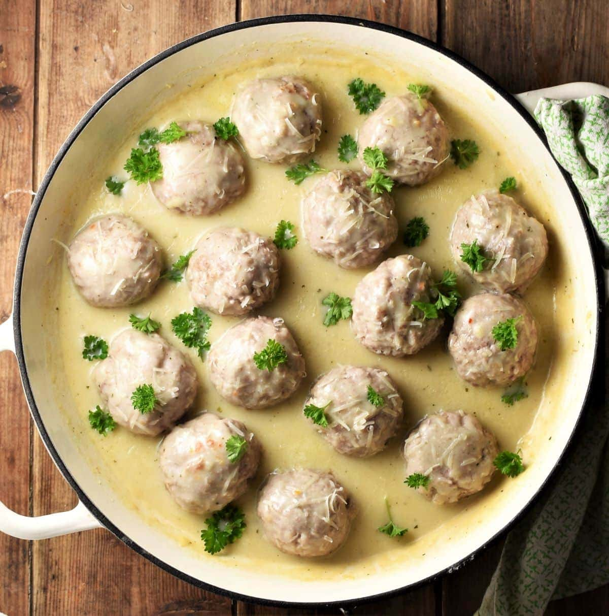 Meatballs in creamy sauce with parsley in large shallow pan.