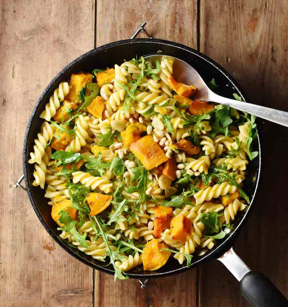Pasta with pumpkin and arugula in pan with spoon.