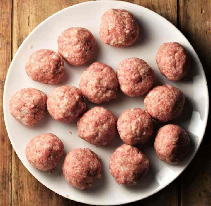Raw meatballs on top of white plate.