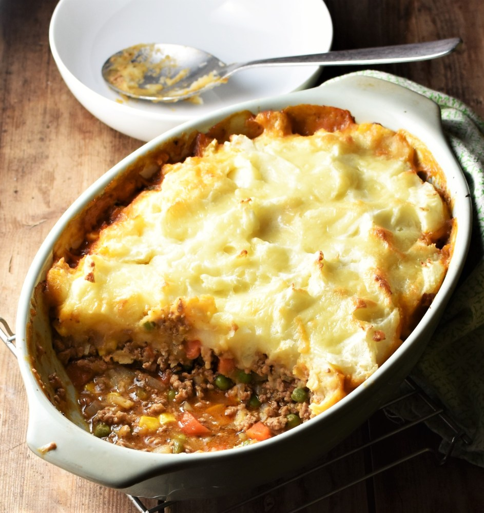 Side view of turkey cottage pie in oval green dish with white bowl and spoon in background.
