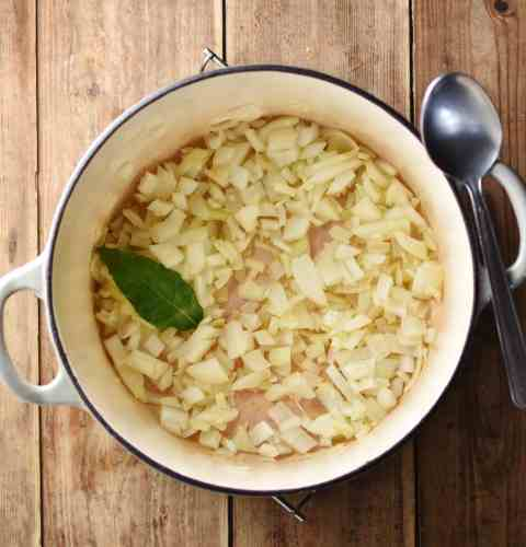 Fried onion with bay leaf inside white pot with spoon to the right.