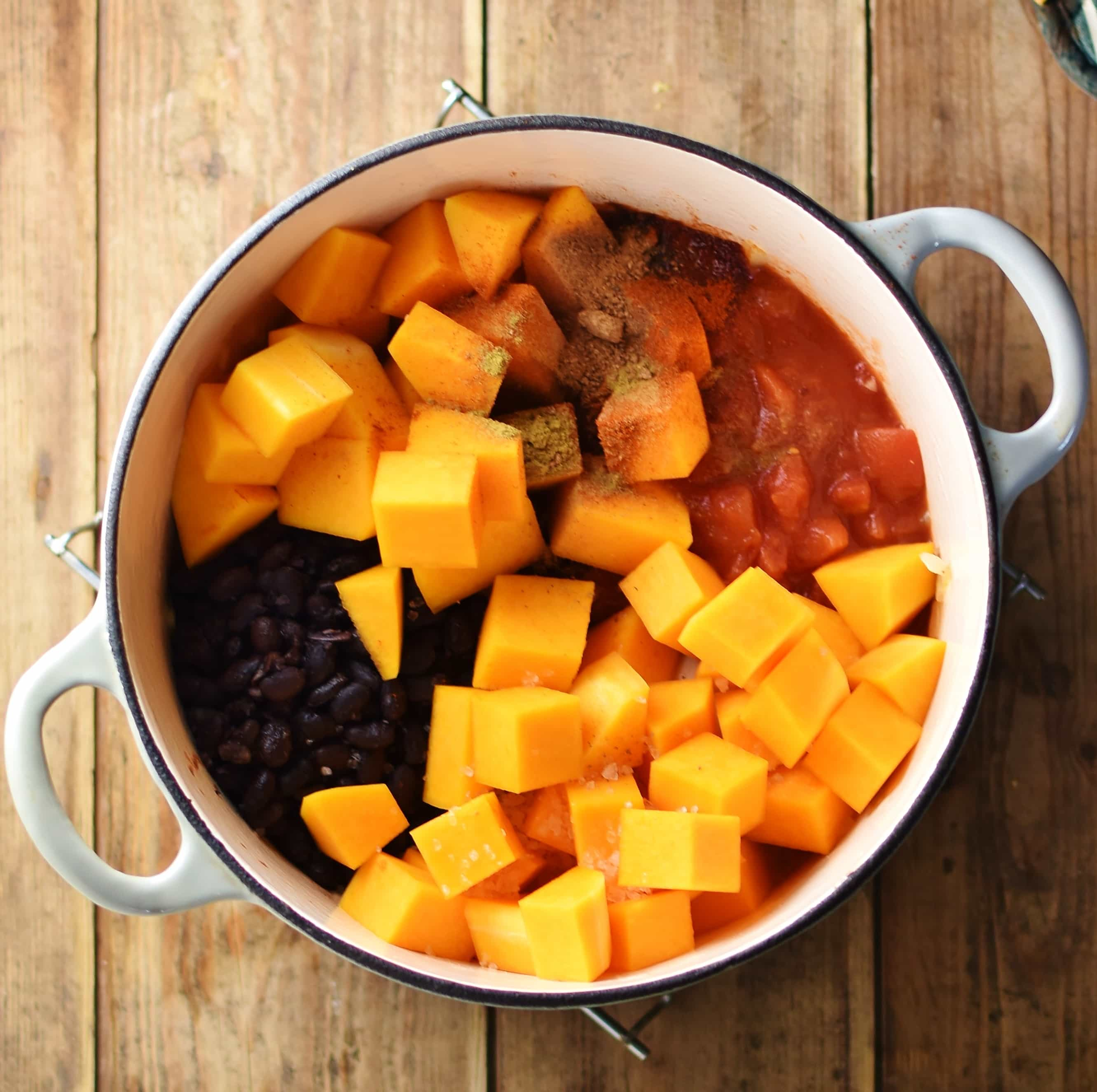 Cubed butternut squash, black beans, tomatoes and spices in white pot.