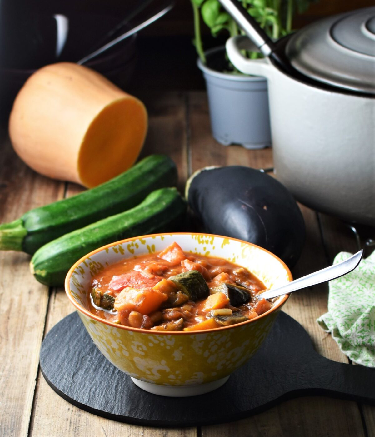 Side view of vegetable stew in yellow patterned bowl with spoon, zucchini, eggplant, squash and pot in background.