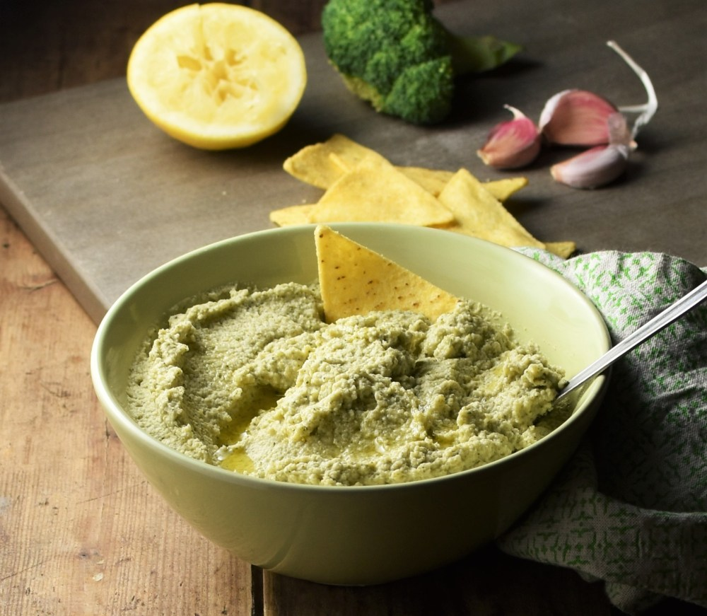 Broccoli dip in green bowl with spoon, nachos, lemon, broccoli and garlic in background.