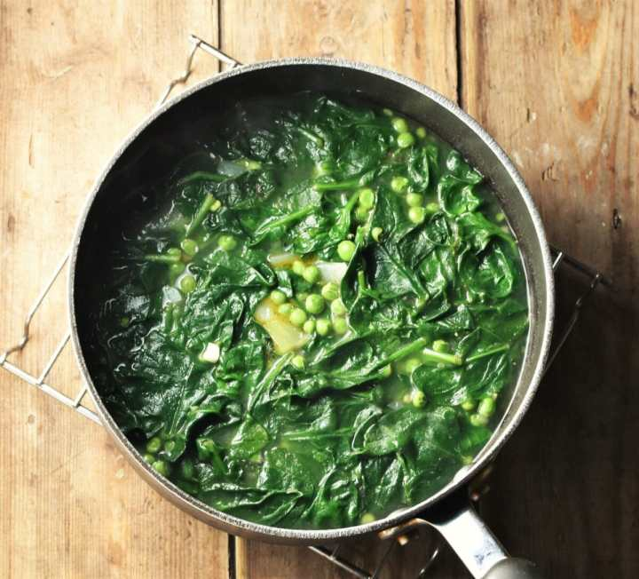 Spinach and peas in large pot with stock.