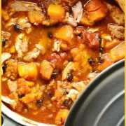 Chicken butternut squash casserole with black beans in white pot with grey lid and green cloth.