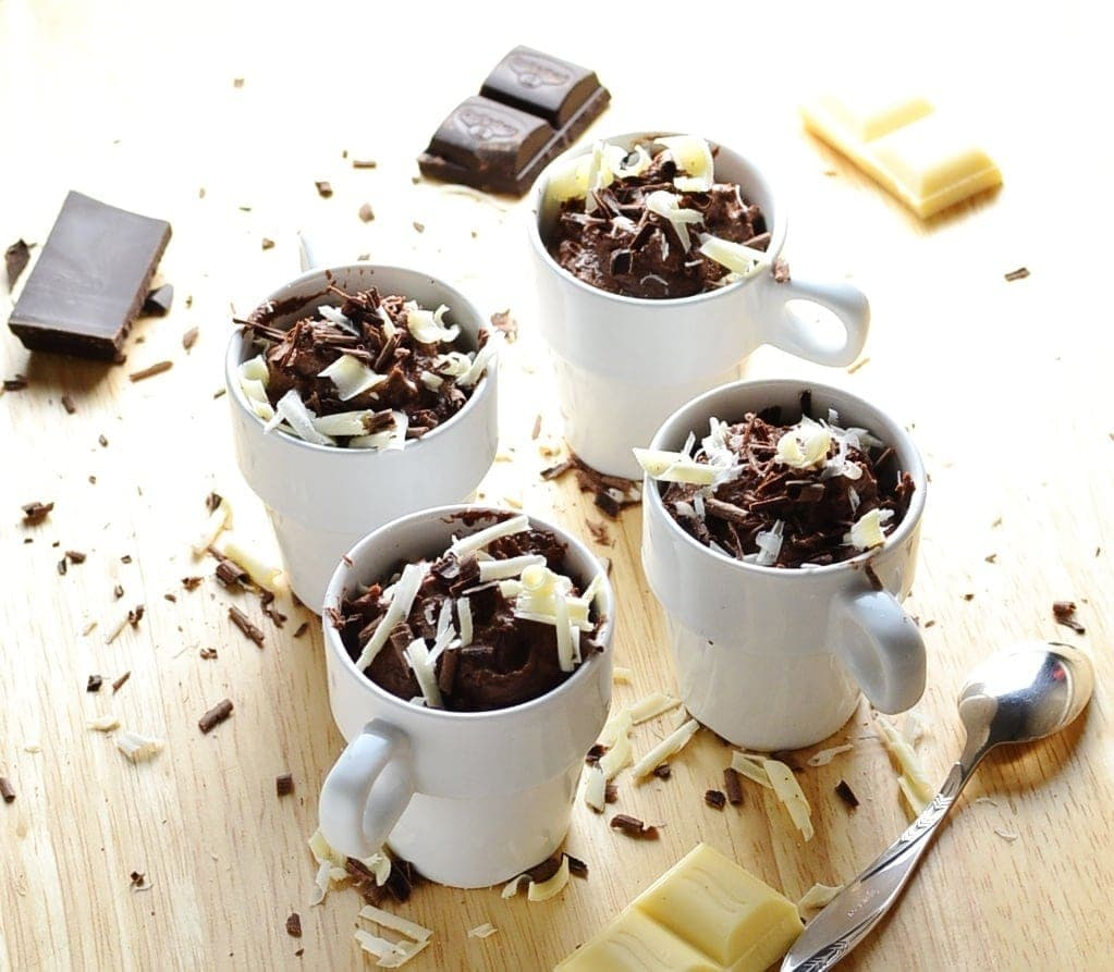 Chocolate cheesecake pots with chocolate shavings, chocolate pieces and spoon on wooden surface.