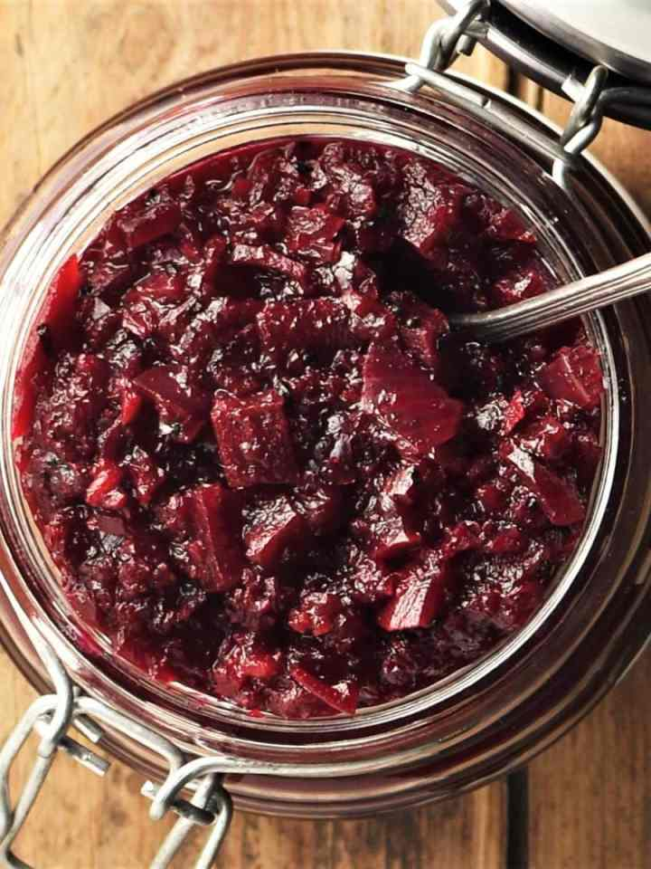 Top down view of beetroot chutney in open jar with spoon.