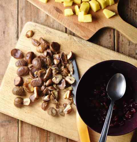 Chopped chestnuts, marzipan, and knife on top of wooden boards, with cranberries in purple bowl with spoon.