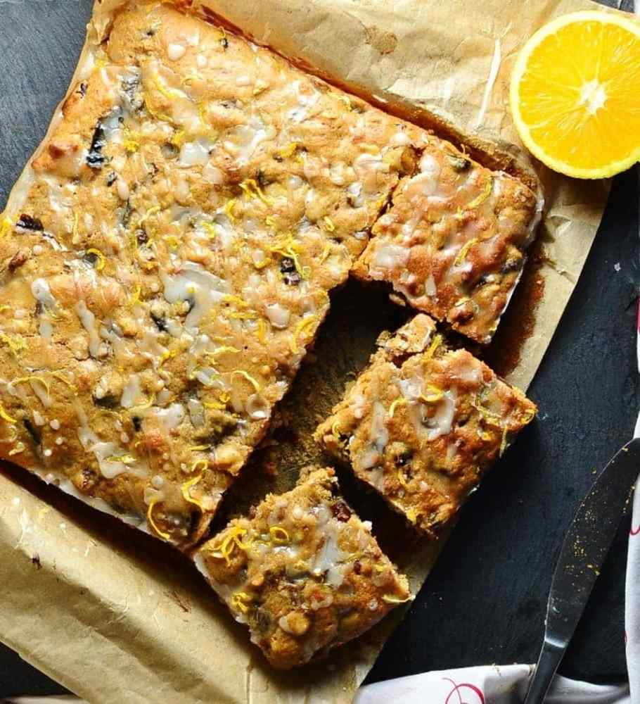 Top down view of fruit cake on top of parchment paper with halved orange and knife.