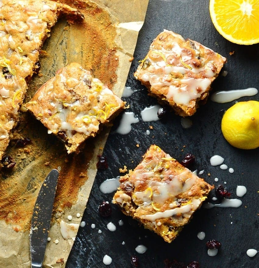 Fruit cake squares on top of dark table and parchment paper, with orange, lemon and knife.