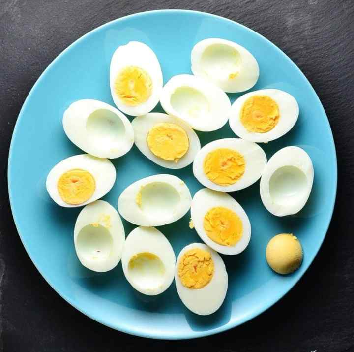 Top down view of hard boiled egg halves on blue plate on grey surface.
