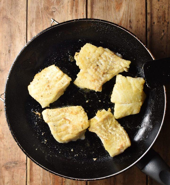 Fried fish fillets in skillet.