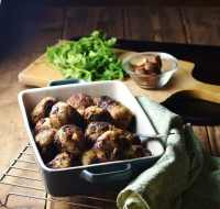 Stuffing meatballs in square blue dish with green cloth to the right, herbs and chestnuts in small dish in background.