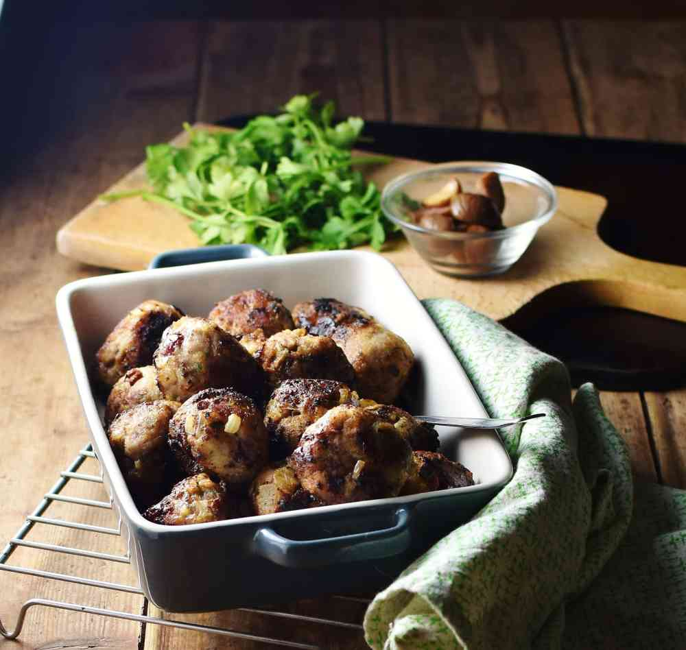 Stuffing balls in square blue dish with green cloth to the right, herbs and chestnuts in small dish in background.