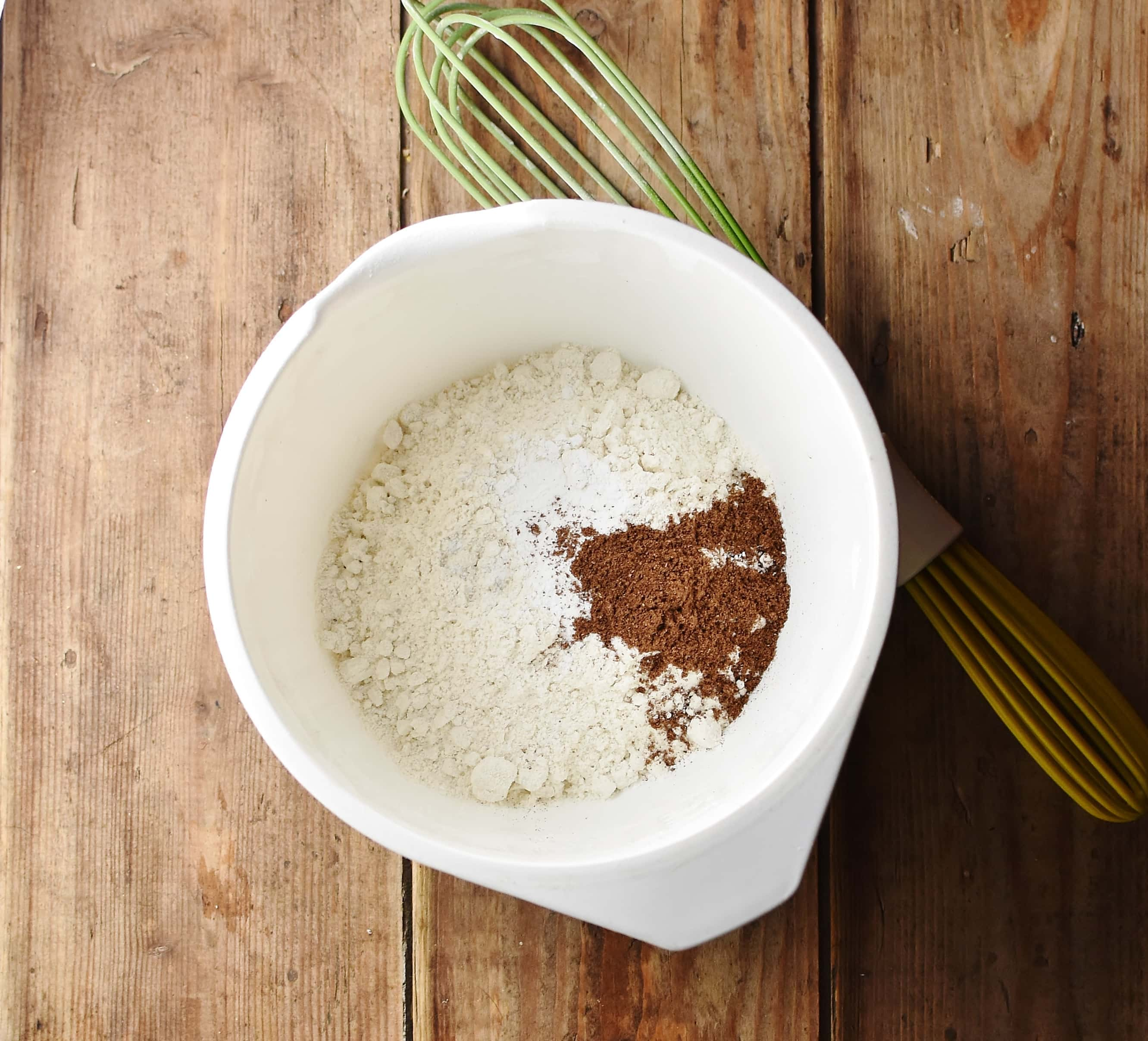 Flour and spices in white bowl with green whisk to the right.
