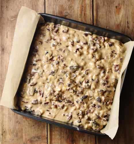 Unbaked fruit cake in square cake pan lined with parchment paper.