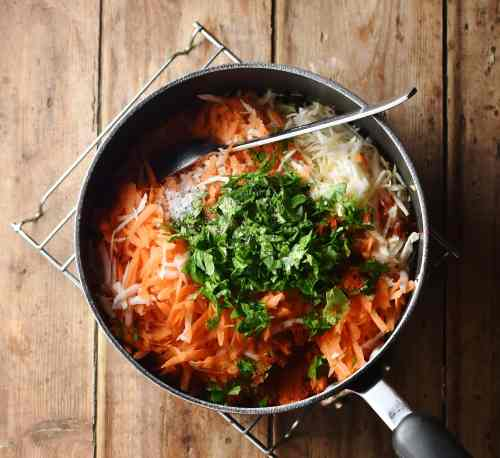 Grated vegetables and herbs in large pot with spoon.