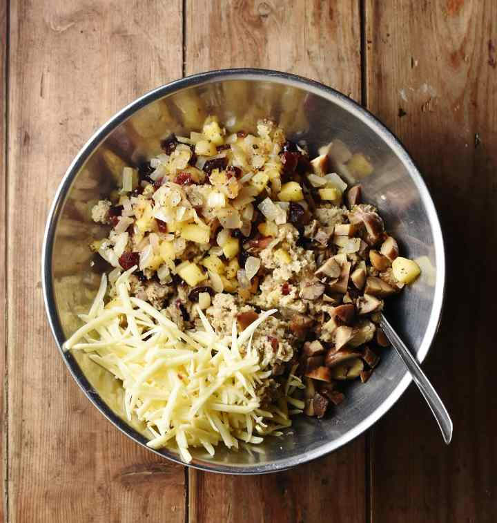 Chopped chestnuts, grated cheese and sausage mixture in large metal bowl with spoon.