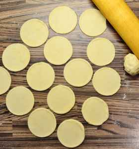 Rolled out pierogi dough with round dough shapes and rolling pin in top right corner.