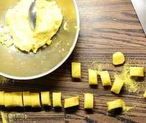 Dumplings mixture with spoon in metal bowl and dumplings scattered around.