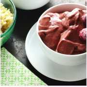 Raspberry smoothie in 2 white bowls with 1 saucer, fresh raspberries in background and green cloth in bottom left corner.