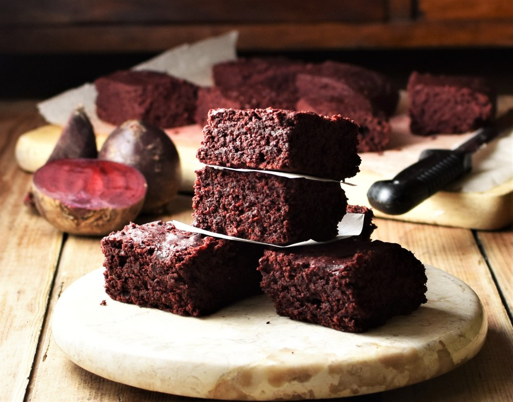 Side view of beetroot brownies on top of round marble plate, with raw beets and brownies in background.