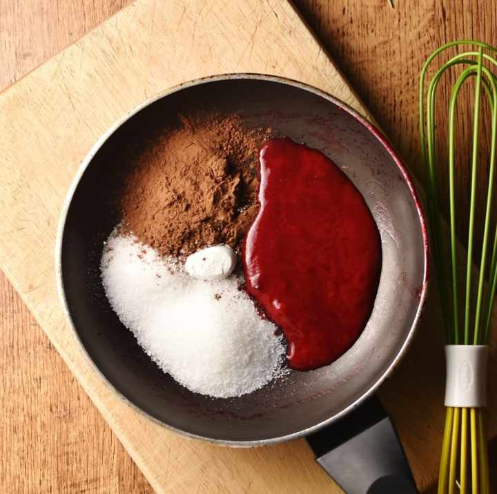Raspberry sauce, cocoa and sugar in pan on top of wooden board with green whisk to the right.