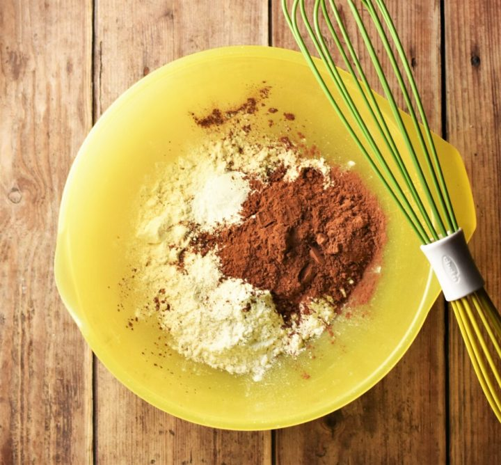 Flour and cocoa powder in large yellow bowl with green whisk.