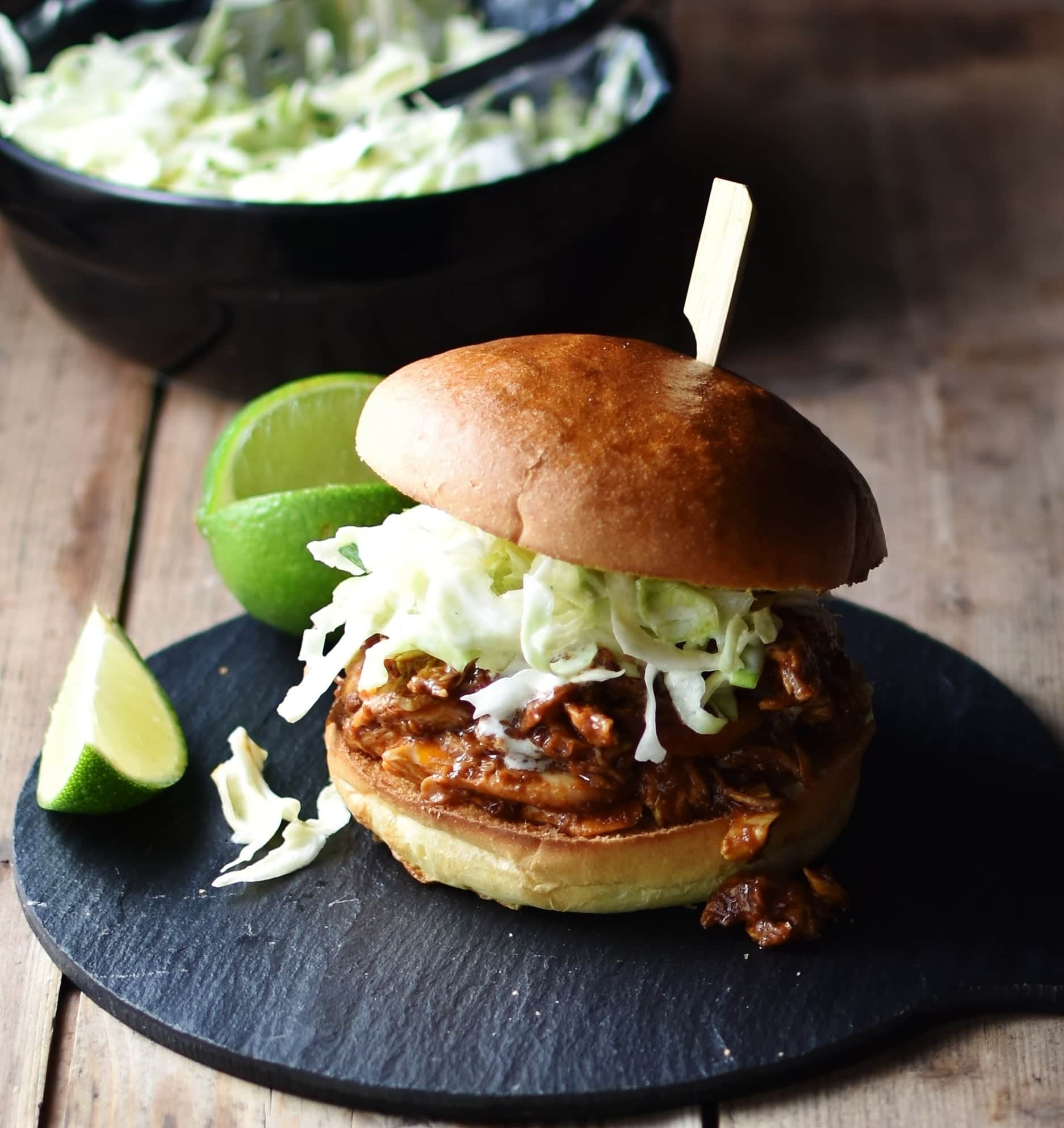 Side view of shredded chicken with coleslaw inside burger bun pierced with bamboos stick, with lime and coleslaw in black dish in background.