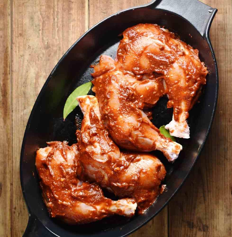 Chicken legs coated in marinade inside black oval dish.