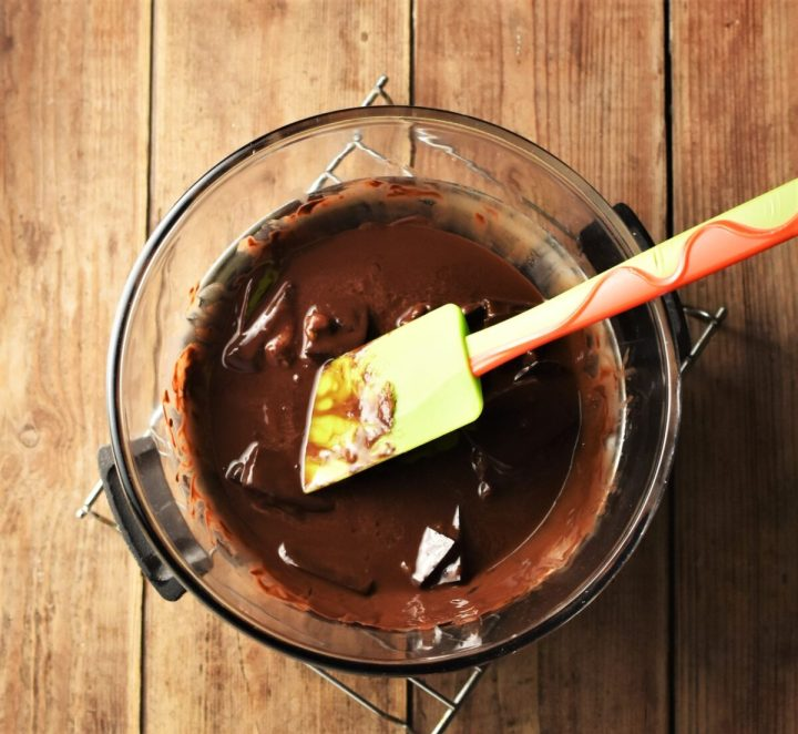 Melted chocolate in mixing bowl with green spatula.