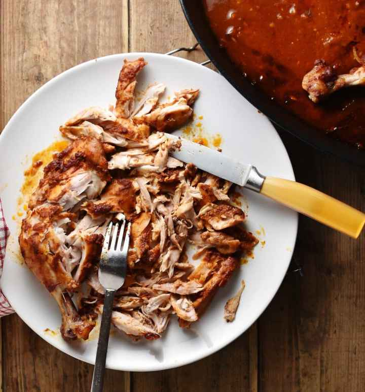 Shredded chicken with knife and fork on top of white plate.