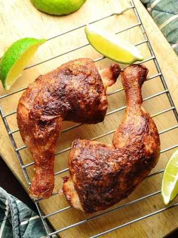Top down view of 2 crispy chicken leg quarters on top of wire rack with lime wedges on top of wooden board.