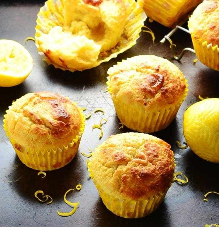Lemon muffins with lemon and zest on dark brown tray.