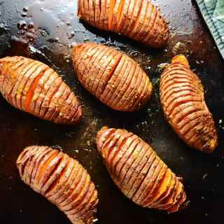 Vegan hasselback sweet potatoes on dark brown oven tray.