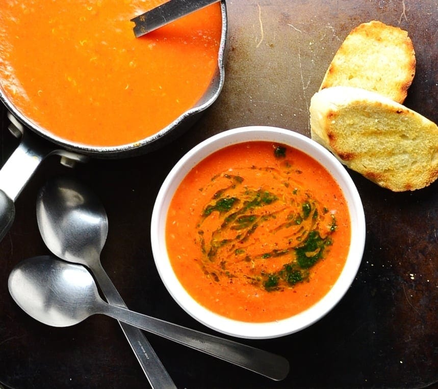 Top down view of red pepper tomato soup with basil in white bowl and black saucepan with toasted baguette slices in top right corner and two spoons in bottom left corner.
