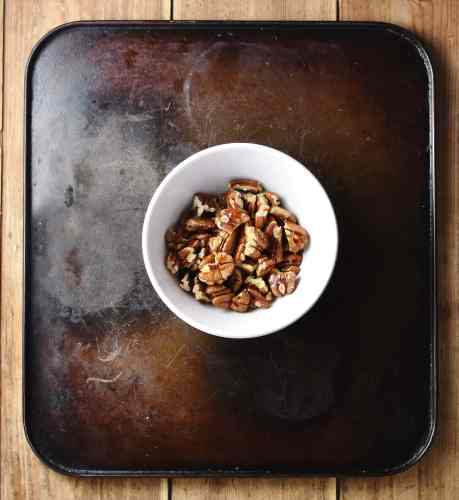 Chopped pecan nuts with maple syrup in small white bowl.