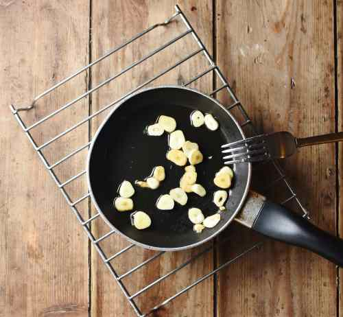 Slices of garlic in small pan with fork on rack.