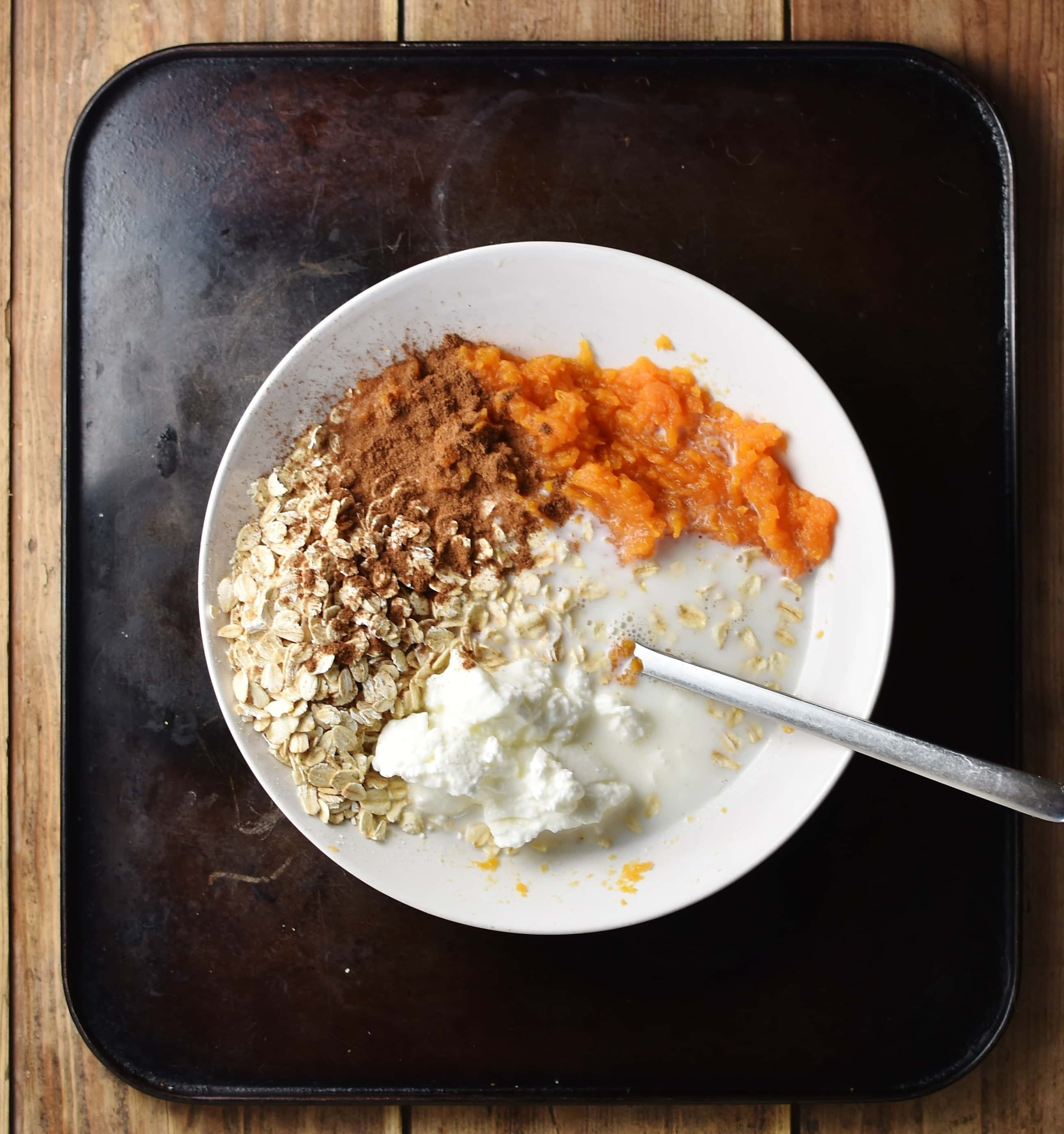 Top down view of oats, milk, spice, yogurt and mashed sweet potato in white bowl with spoon.