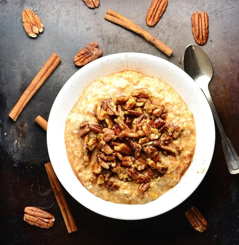 Top down view of sweet potato overnight oats with maple pecans on top of dark surface with spoon and cinnamon sticks and pecans scattered about.