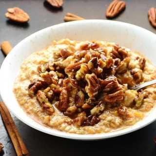Side view of sweet potato overnight oats with pecans and spoon in white bowl on top of dark table with cinnamon sticks and pecans scattered about.