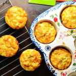 Top down view of sweet potato egg muffins in ceramic muffin dish and on top of cooling rack, with green spatula at top.