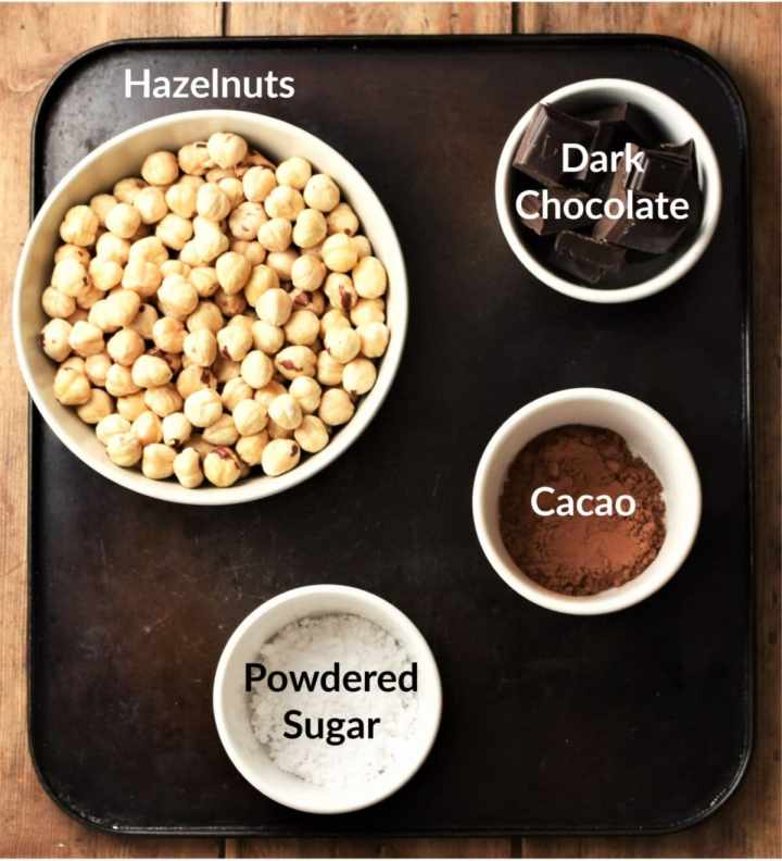 Blanched hazelnuts, icing sugar, chocolate pieces and cocoa in individual bowls.