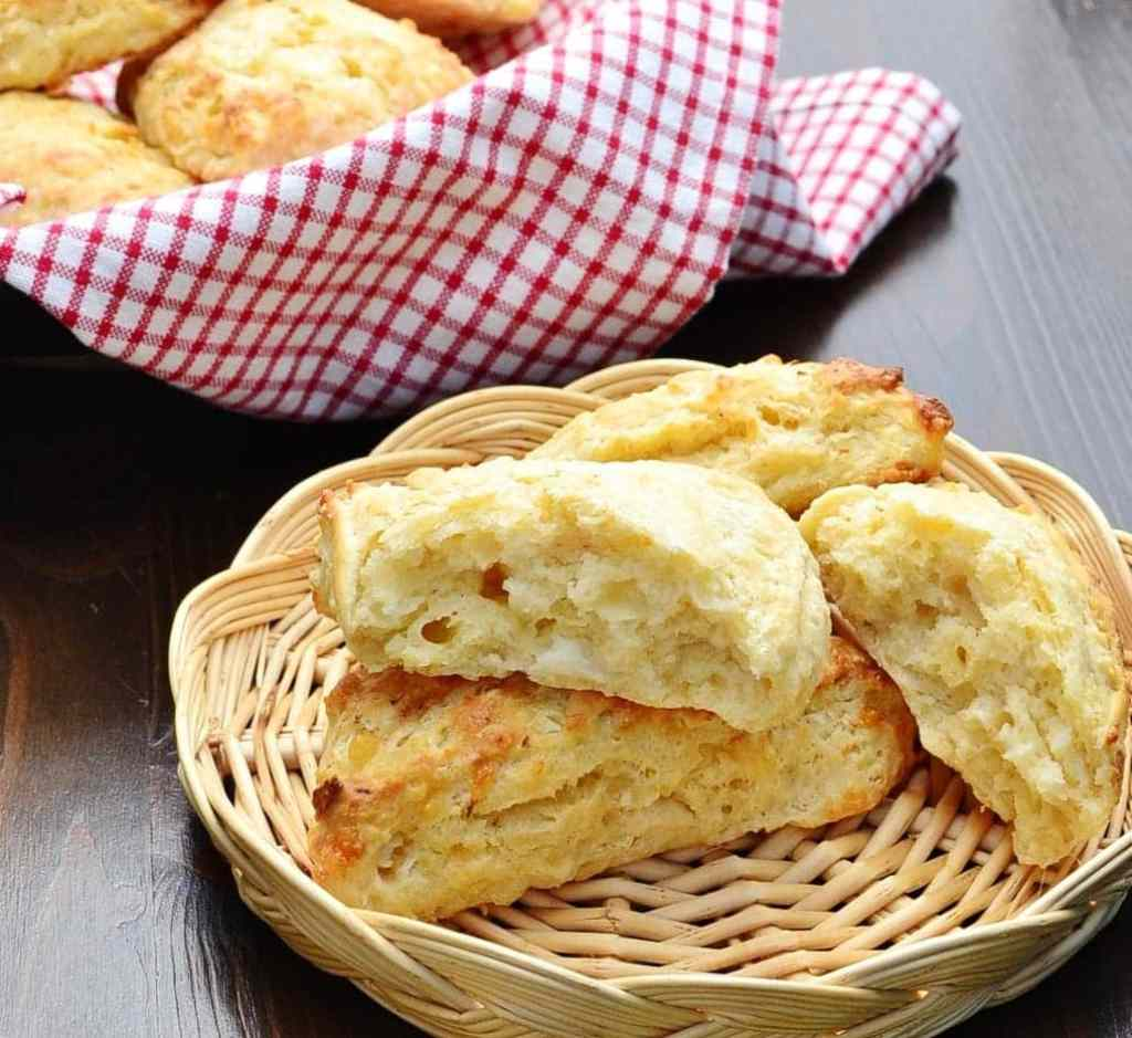 Cheese scones inside basket with more scones wrapped in red-and-white cloth in background.