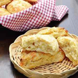 Cheese scones in basket with red-and-white checkered cloth with scones in background.